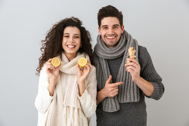 Photo d'un couple en bonne santé homme et femme portant des écharpes tenant des citrons et du gingembre, isolé sur mur gris