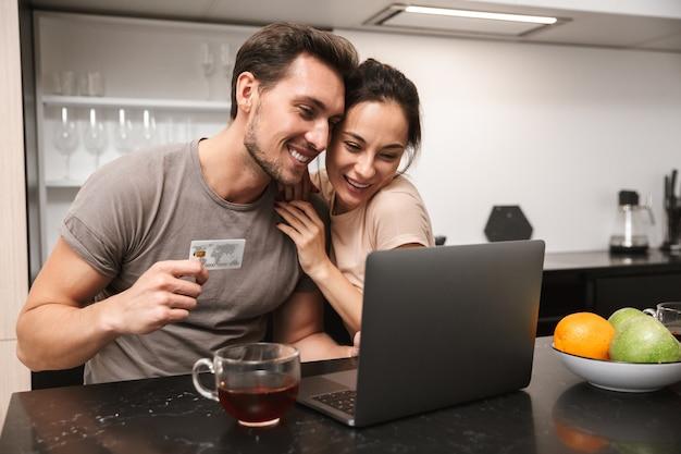 Photo de couple brunette homme et femme utilisant un ordinateur portable avec carte de crédit, assis dans la cuisine