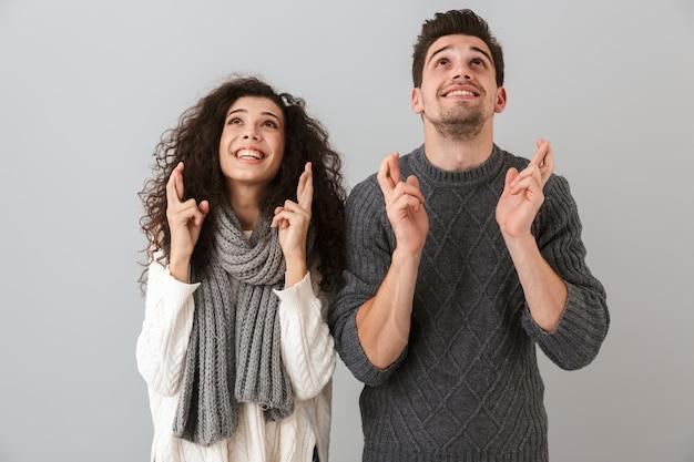 Photo de couple européen homme et femme souriant et debout avec les doigts croisés, isolé sur mur gris