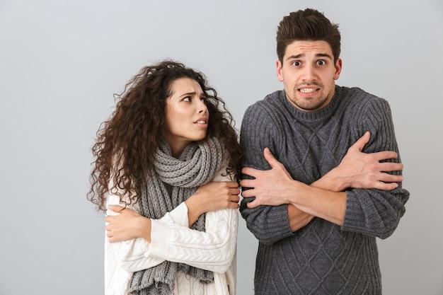 Photo de couple gelé homme et femme portant des écharpes tremblant et se serrant, isolé sur mur gris