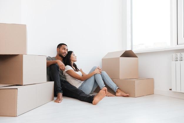 Photo d'un couple heureux assis avec des boîtes déballées. homme tenant la clé. en regardant de côté.