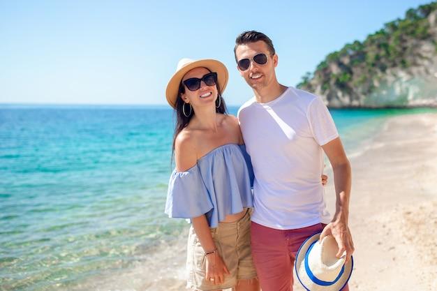 Photo d'un couple heureux à lunettes de soleil sur la plage