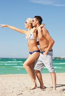 Photo d'un couple heureux à lunettes de soleil sur la plage.