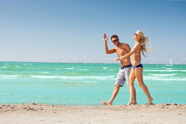 Photo d'un couple heureux marchant sur la plage.