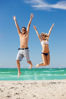 Photo d'un couple heureux sautant sur la plage.