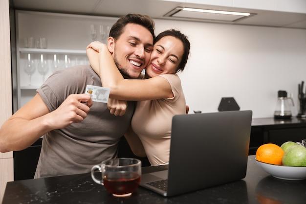 Photo de couple moderne homme et femme utilisant un ordinateur portable avec carte de crédit, assis dans la cuisine