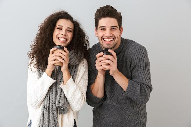 Photo de couple souriant homme et femme portant des écharpes tenant des tasses avec du thé ou du café chaud, isolé sur mur gris
