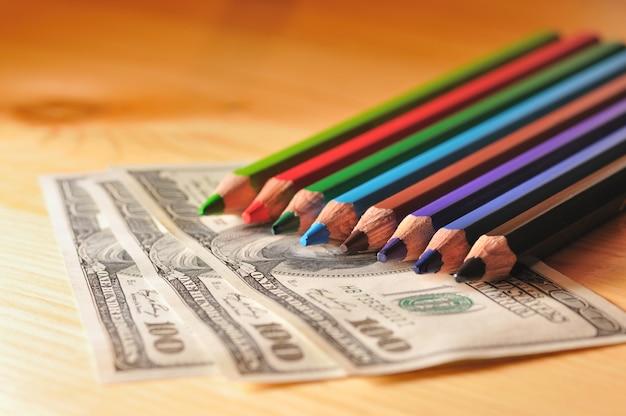 Photo de crayons en bois dans des couleurs vives vert et violet dans le contexte d'un billet d'un dollar