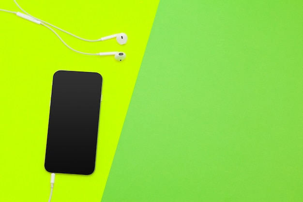 Photo de création à plat du bureau de l'espace de travail avec écouteurs et téléphone portable