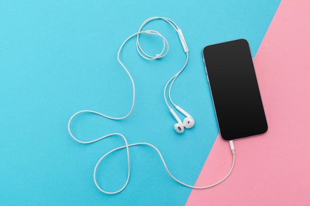 Photo créative à plat du bureau de l'espace de travail avec écouteurs et téléphone mobile