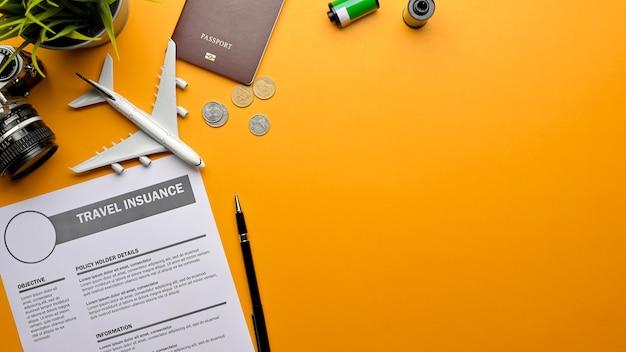 Photo créative à plat du formulaire d'assurance voyage, appareil photo, passeport, modèle d'avion et espace de copie sur fond jaune, vue de dessus