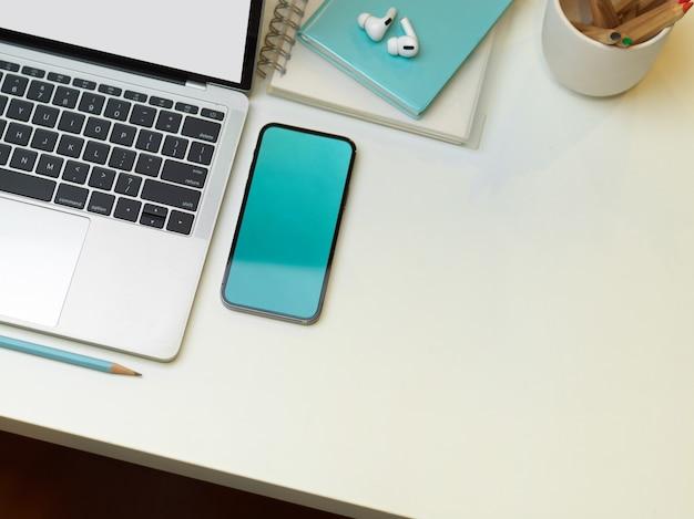 Photo créative à plat de l'espace de travail moderne avec ordinateur portable, smartphone, papeterie et espace de copie