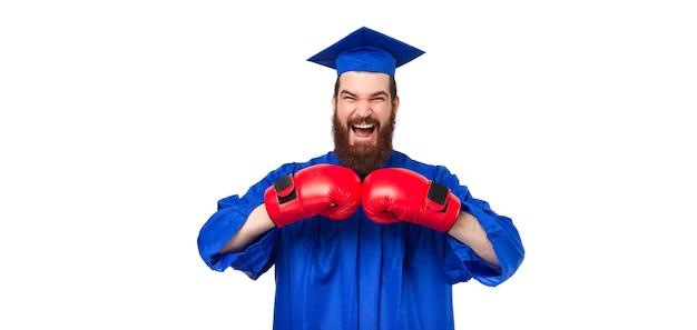 Photo de crier étonné étudiant homme barbu en célibataire portant des gants de boxe rouges