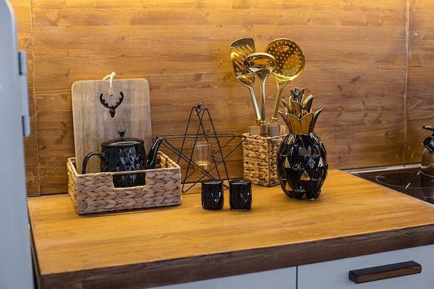 Photo de la cuisine confortable avec table marron et beaucoup d'ustensiles de cuisine dessus