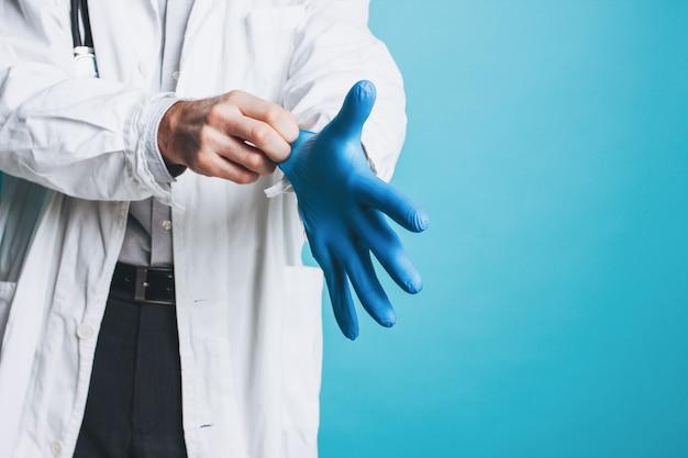Photo de culture de l'homme médecin en blouse blanche met des gants médicaux en caoutchouc isolé sur fond bleu