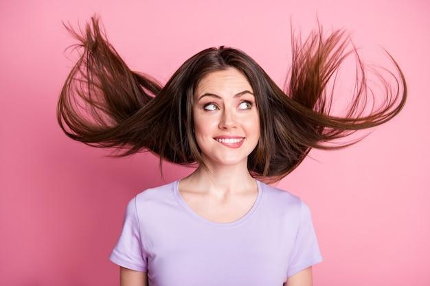Photo d'une curieuse fille positive se mordre les lèvres imaginer que la coiffure de la mouche aérienne porte des vêtements de bonne apparence isolés sur un fond de couleur rose