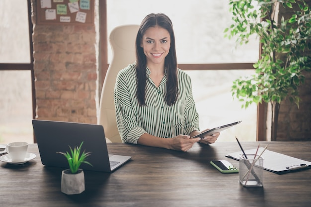 Photo de dame chef assis table tenir tablette dans bureau loft