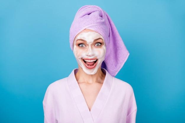 Photo d'une dame étonnée masque en mousse bouche ouverte sourire brillant porter une serviette violette turban peignoir isolé fond de couleur bleu
