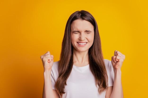 Photo d'une dame étonnée qui lève les poings porte un t-shirt blanc posant sur fond jaune
