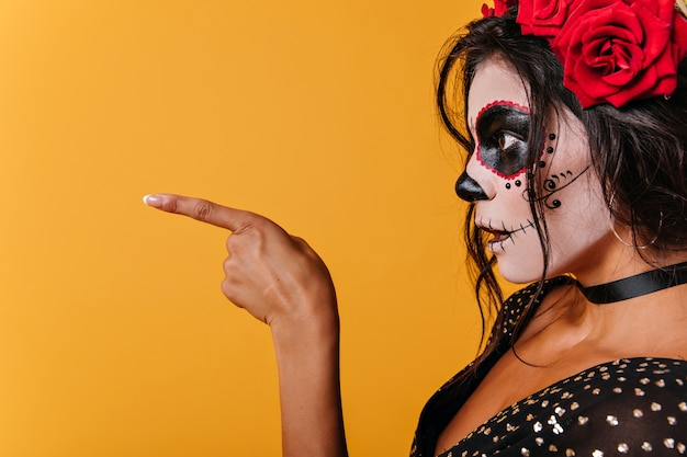Photo de dame en haut noir de profil. fille avec le maquillage du crâne dans la surprise montre doigt à côté