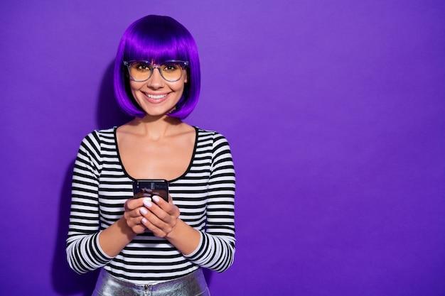 Photo de dame satisfaite tenant par la main nouveau téléphone heureux d'obtenir des spécifications d'usure d'achat pull rayé fond violet isolé