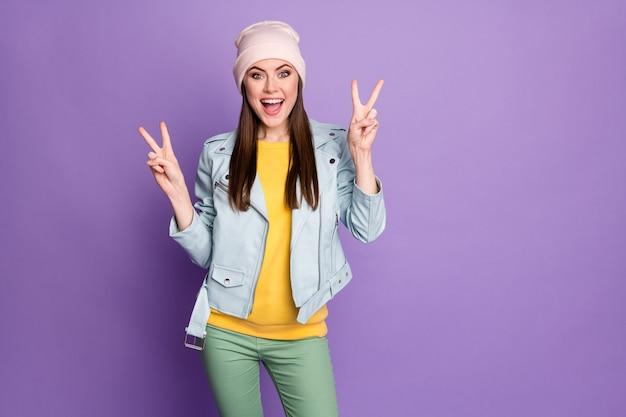 Photo d'une dame séduisante et funky de bonne humeur montrant des symboles de signe v mains personne joyeuse adolescent porter un chapeau décontracté bleu pantalon de veste moderne isolé fond de couleur pourpre