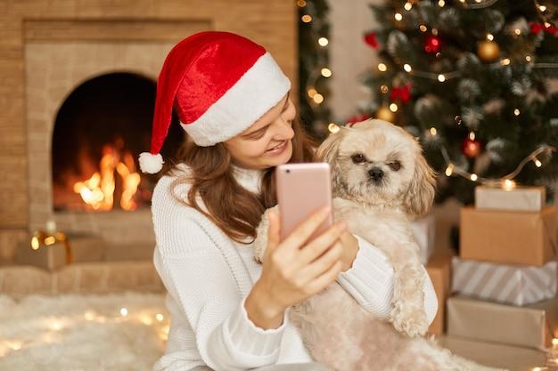 Photo de dame souriante avec chien à noël, posant dans la salle de fête près de la cheminée et prenant selfie ou ayant un appel vidéo, dame regardant son animal de compagnie avec le sourire et tenant le téléphone dans les mains.
