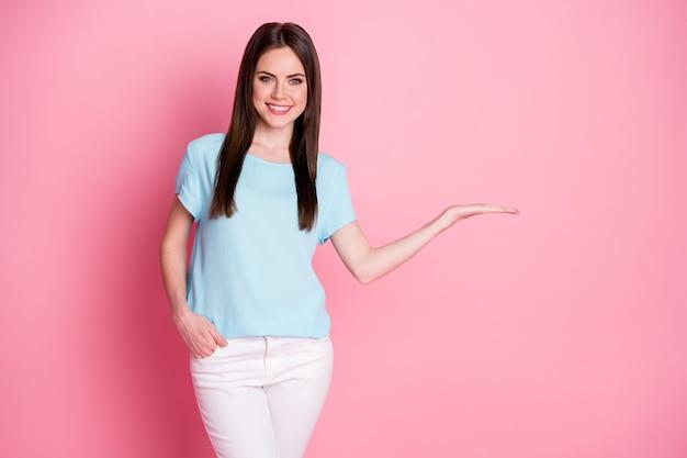 Photo de dame tenir bras ouvert espace vide présent vente produit porter t-shirt décontracté pantalon blanc isolé fond de couleur rose
