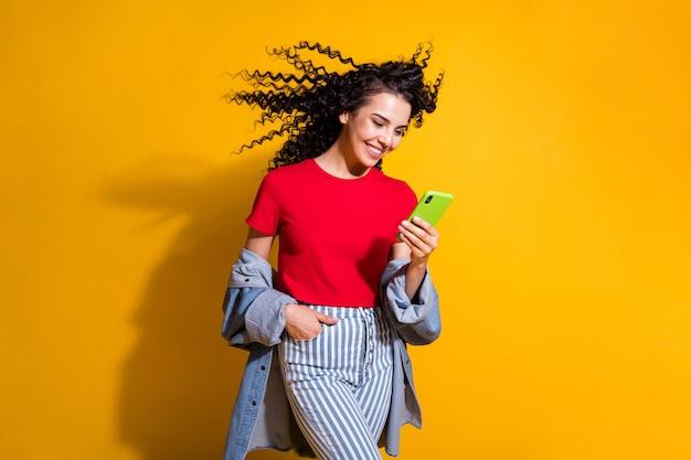Photo de dame tenir téléphone vent souffler les cheveux porter des jeans rayés recadrée veste t-shirt rouge isolé fond de couleur jaune