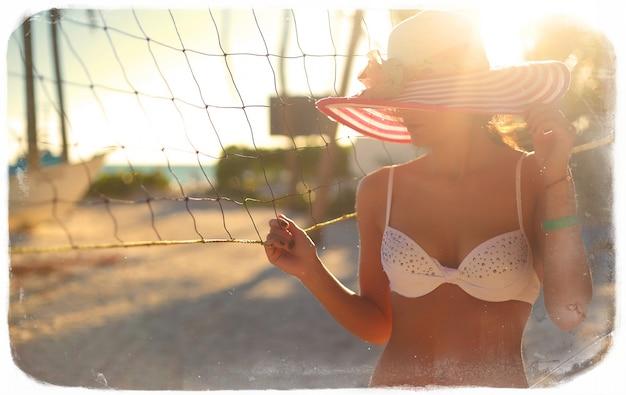 Photo dans un style rétro de fille modèle sexy en bikini blanc avec filet de volley-ball sur la plage et les palmiers derrière le ciel d'été bleu