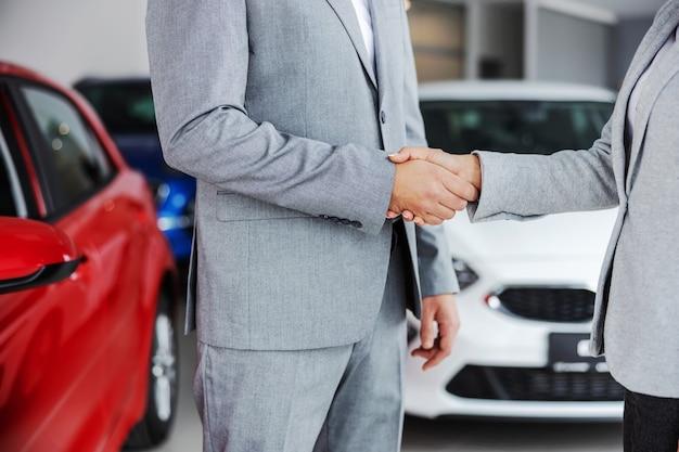 Photo découpée du vendeur de voiture serrant la main de l'acheteur en se tenant debout dans le salon de l'automobile.