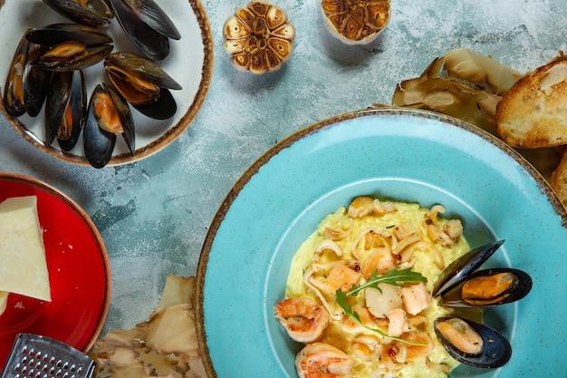 Photo de délicieux risotto au safran et fruits de mer sur table.