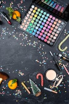 Photo de dessus d'accessoires pour maquilleuse, mandarine, sapin de noël, canne à sucre sur table noire avec place pour le texte au centre