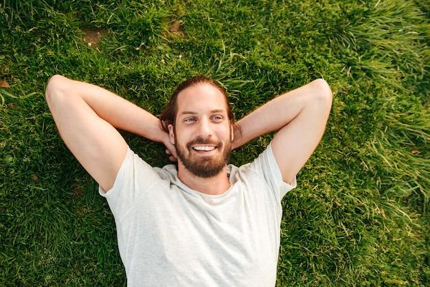 Photo de dessus d'un bel homme barbu de 30 ans portant un t-shirt blanc allongé sur l'herbe dans un parc verdoyant, mettant les mains derrière le dos