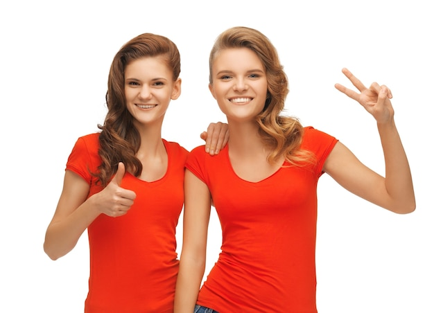 Photo de deux adolescentes montrant les pouces vers le haut et le signe de la victoire