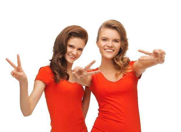Photo de deux adolescentes en t-shirts rouges montrant le signe de la victoire