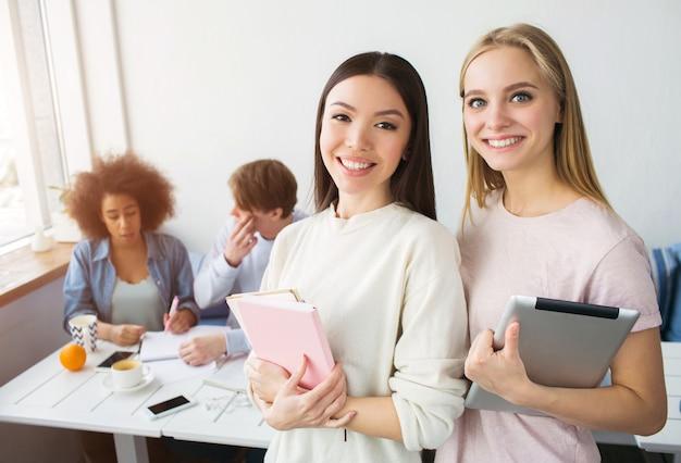 Une photo de deux belles filles asiatiques debout et souriant. brunette tient un cahier rose tandis que la fille blonde a une tablette dans les mains. là, leurs frondes s'asseyaient derrière eux et étudiaient.