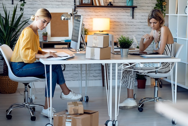 Photo de deux belles vendeuses indépendantes travaillant avec un ordinateur et une tablette numérique dans leur petite entreprise en démarrage.