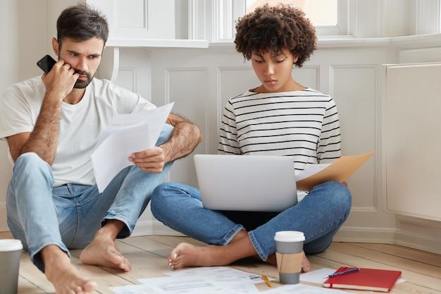 Photo de deux collègues métis lisant la documentation, concentrés sur la résolution de problèmes de planification