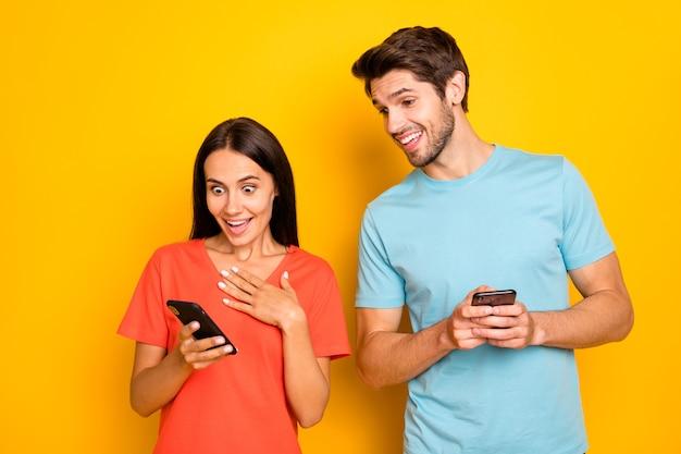 Photo de deux drôles de gars dame personnes couple tenir des téléphones montrant de nouveaux bons commentaires ne pas croire que les yeux portent des t-shirts occasionnels bleu orange isolé mur de couleur jaune