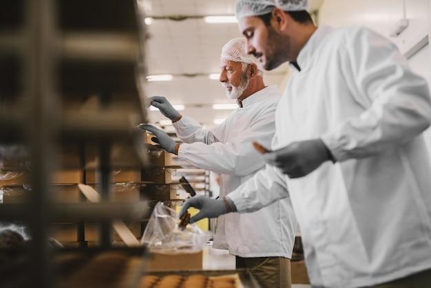 Photo de deux employés masculins d'une usine alimentaire dans des vêtements stériles emballant des biscuits fraîchement préparés. debout dans une pièce lumineuse.