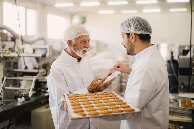 Photo de deux employés en vêtements stériles dans une usine alimentaire souriant et parlant. le jeune homme tient un plateau plein de biscuits frais tandis que le plus âgé tient la tablette et vérifie le processus de production.