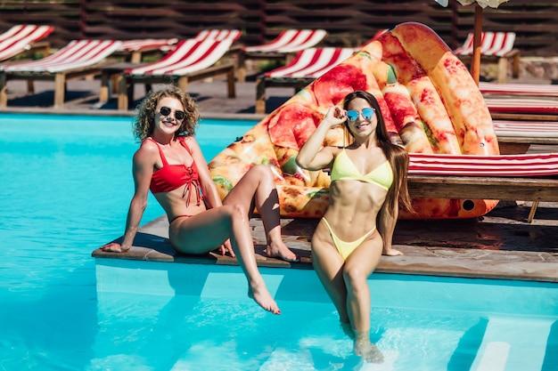 Photo de deux femmes assises près de la piscine, un flotteur moderne derrière et se relaxant dans la piscine. joie.