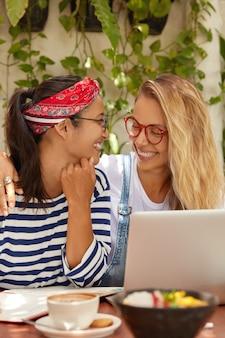 Photo de deux femmes joyeuses regardent avec des sourires