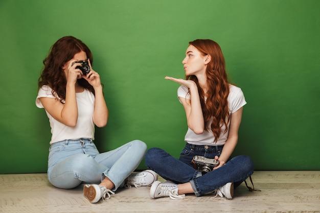 Photo de deux filles rousses de 20 ans assis sur le sol avec les jambes croisées et jouant dans les paparazzi avec photopraphing sur appareil photo rétro, isolé sur fond vert