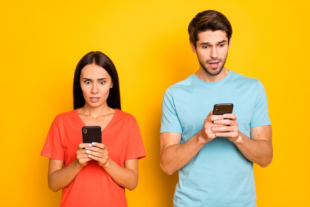 Photo de deux gars dame personnes couple tenir téléphone mains lecture commentaires négatifs post bouche ouverte porter des t-shirts orange bleu décontracté mur de couleur jaune isolé