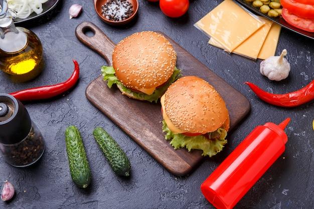 Photo de deux hamburgers sur planche de bois, fromage
