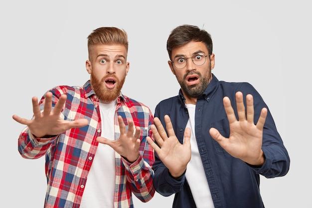 Photo de deux hommes ayant des expressions effrayées, faisant un geste effrayé avec les paumes, essayant de se défendre contre quelque chose de mal