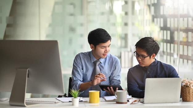 Photo de deux hommes intelligents travaillant ensemble avec un ordinateur portable et une tablette tout en étant assis au long bureau de travail sur un bureau moderne.