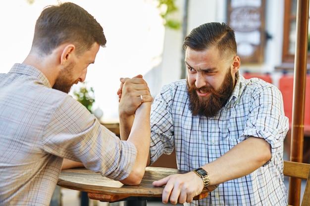 Sur la photo, deux hommes s'affrontent sur des bras reslings